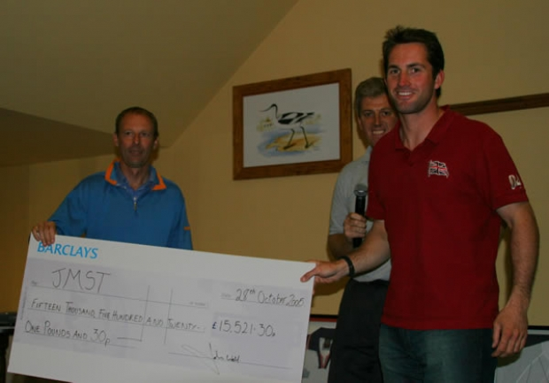 Ben Ainlsie receives the cheque on behalf of the John Merricks Sailing Trust