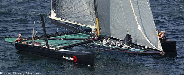 The all-carbon Alinghi catamaran weighs less than an Etchell. Bertarelli helms while the crew sit out to leeward